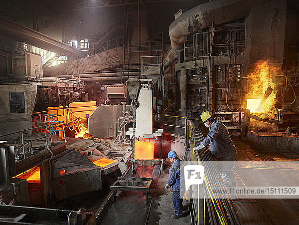 Industry  Worker lifting copper plates with indoor crane for cooling in water basin