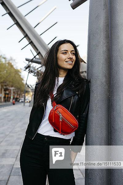 Glückliche junge Frau mit roter Hüfttasche in der Stadt