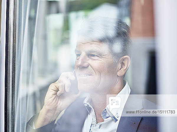 Portrait of mature businessman on cell phone