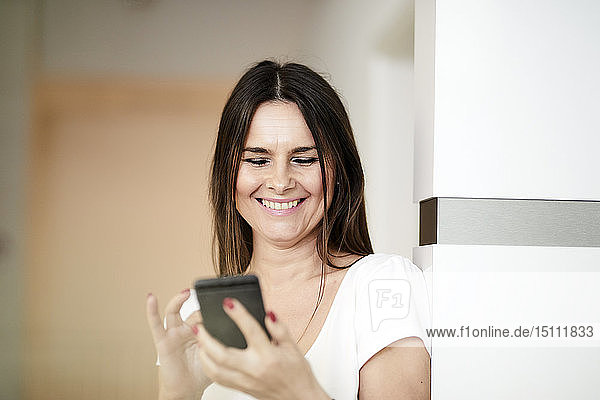 Portrait of smiling woman in an office using cell phone