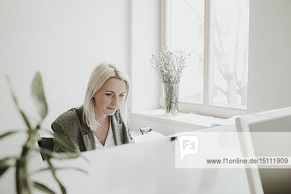 Junge Frau arbeitet am Schreibtisch im Büro
