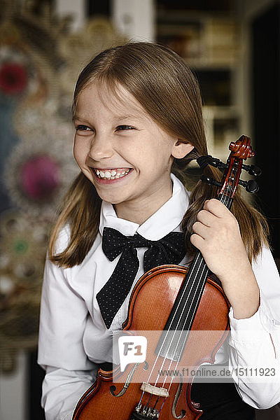 Portrait of a happy girl with a violin at home
