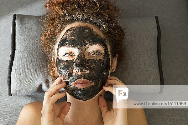 Porträt einer liegenden jungen Frau mit Gesichtsmaske