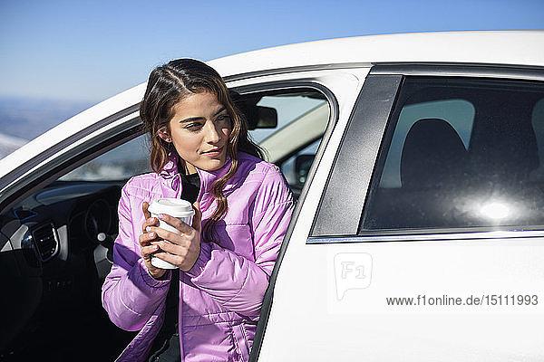 Frau sitzt im Auto und trinkt vor dem Skifahren einen heißen Kaffee
