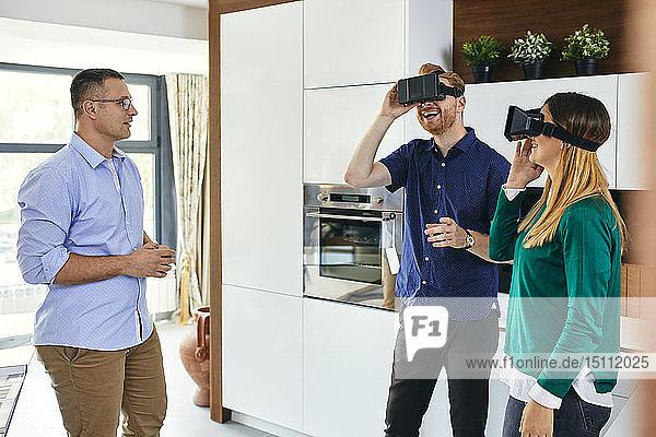 Ehepaar mit VR-Brille beim Einkaufen für eine neue Küche im Ausstellungsraum