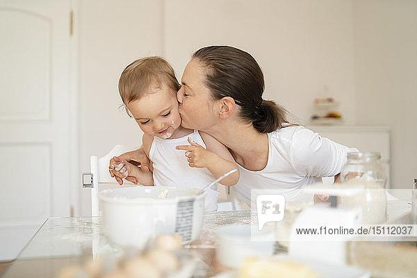 Mutter küsst kleine Tochter beim gemeinsamen Kuchenbacken in der heimischen Küche