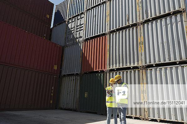 Arbeiter benutzen Tabletten vor Frachtcontainern auf einem Industriegelände
