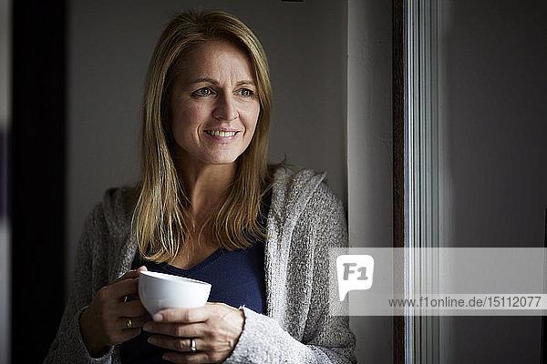 Lächelnde Frau  die Kaffee trinkt und aus dem Fenster schaut