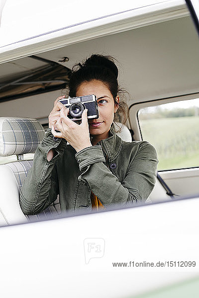 Young woman sitting in camper  taking pictures