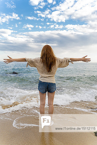 Back view of redheaded young woman standing at seafront with arms outstretched