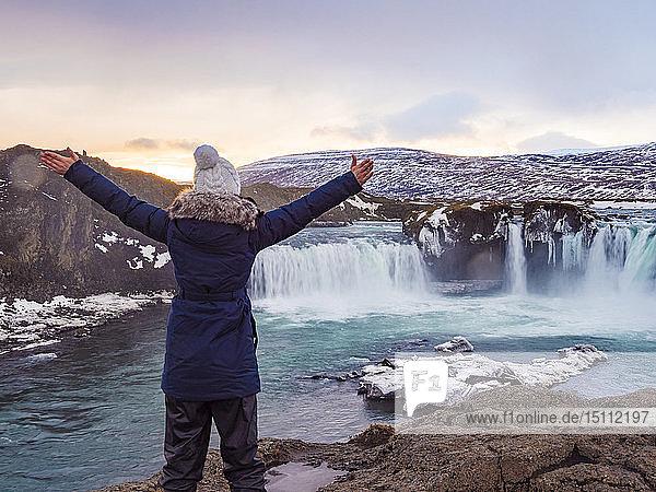 Island  Frau am Godafoss-Wasserfall im Winter