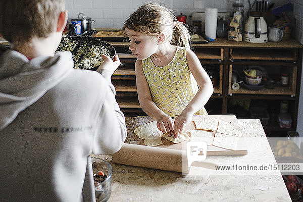 Little girl and her older brother preparing stuffed pastry in the kitchen