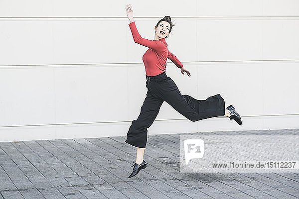 Elegante junge Frauen springen vor eine Mauer