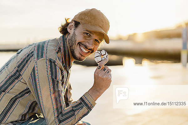 Portrait of laughing man eating doughnut at sunset