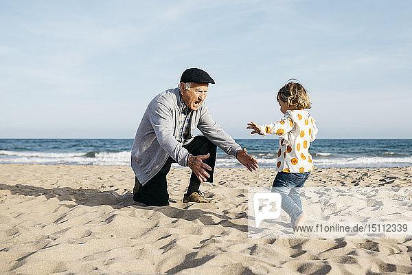 Großvater spielt mit seiner kleinen Enkelin am Strand