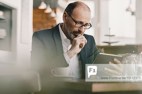 Mature businessman using tablet in a cafe