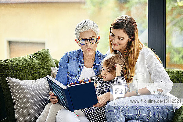 Mother  daughter and granddaughter sitting on couch  reading a book
