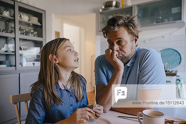 Daughter talking to father in kitchen at home