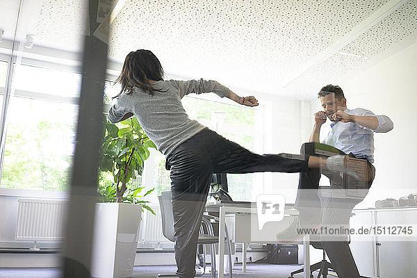 Geschäftsmann und Geschäftsfrau kämpfen im Amt