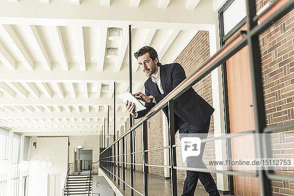 Junger Geschäftsmann steht auf Galerie in modernem Bürogebäude und benutzt digitales Tablet
