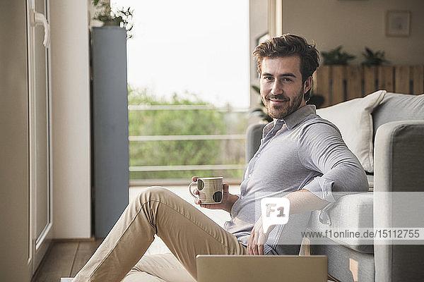 Junger Mann sitzt zu Hause auf dem Boden  benutzt Laptop  trinkt Kaffee