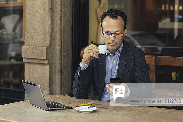 Businessman with laptop in a coffee shop looking at his smartphone