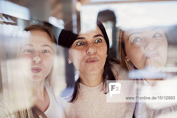 Mutter und Töchter drücken Nasen gegen Fensterscheibe