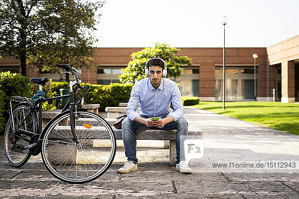 Young man with bicycle using smartphone and listening music