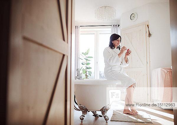 Reife Frau sitzt auf der Badewanne und trägt Wimperntusche auf