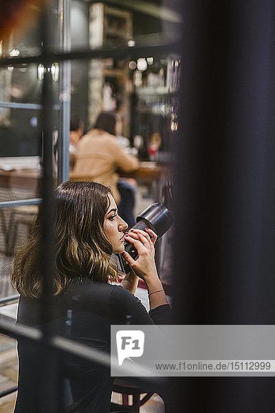 Junge Frau mit Kamera in einer Bar bei Nacht