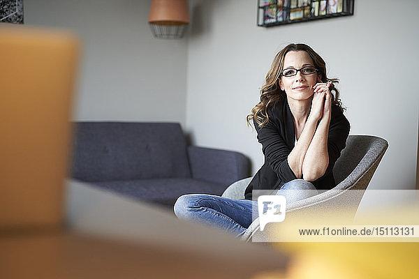 Porträt einer Frau,  die zu Hause auf einem Sessel sitzt