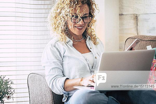 Lächelnde Frau mit Laptop und Handy auf der Couch zu Hause