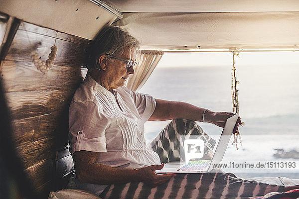 Ältere Frau sitzt im Oldtimer-Van am Meer und benutzt einen Laptop