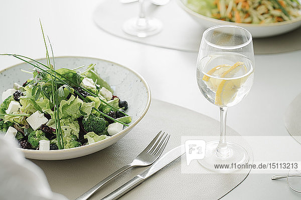 Salat und ein Glas Wasser auf einem Tisch in einem Restaurant