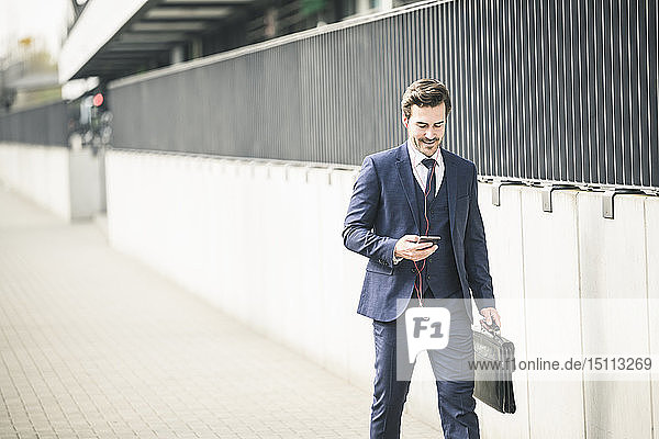 Businessman walking in the city with cell phone and earphones