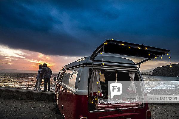 Älteres Ehepaar reist in einem Oldtimer-Van und küsst sich bei Sonnenuntergang am Meer