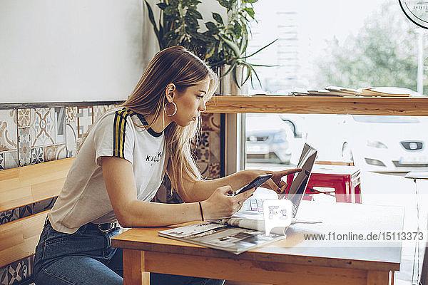 Junge Frau benutzt Mobiltelefon und Laptop im Café