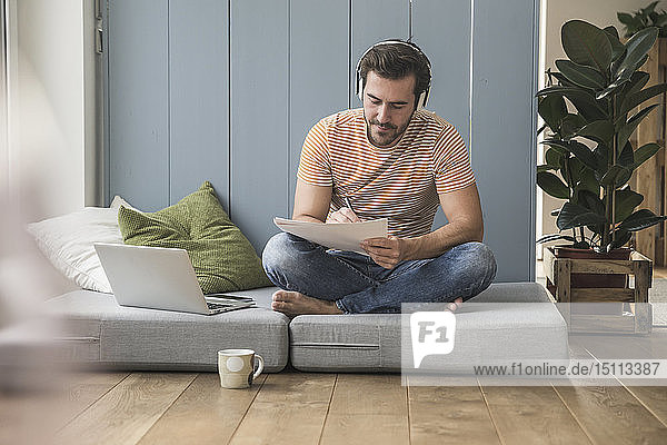 Junge Mama sitzt auf Matratze  macht Notizen  benutzt Kopfhörer