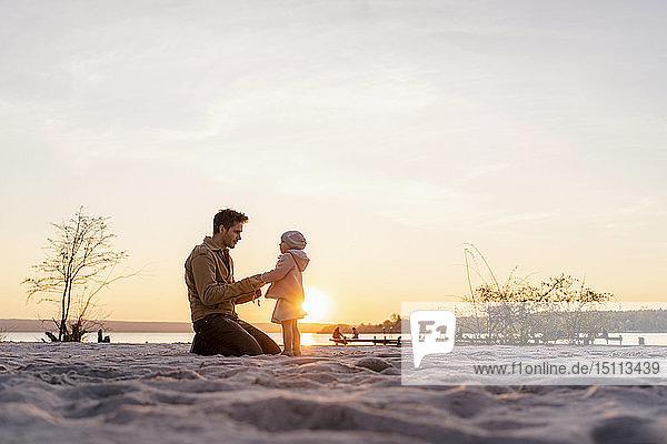 Deutschland  Bayern  Herrsching  Vater und Tochter spielen bei Sonnenuntergang am Strand