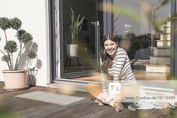 Porträt einer lachenden jungen Frau  die zu Hause auf der Terrasse sitzt