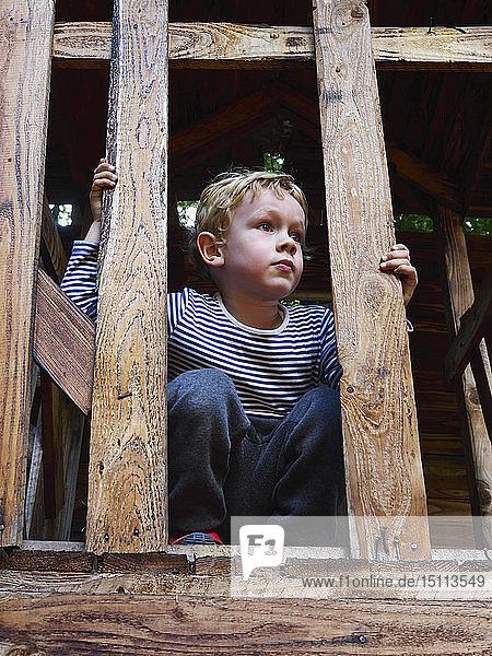 Porträt eines kleinen Jungen  der auf einem Klettergerüst kauert