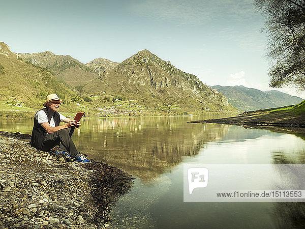 Italy  Anfo  senior man sitting at Lake Idro using tablet