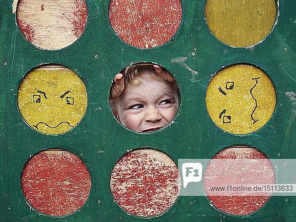 Porträt eines kleinen Jungen  der sich auf einem Spielplatz versteckt