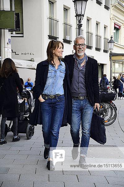Ein reifes Paar  das in der Stadt spazieren geht und die Arme um sich hat