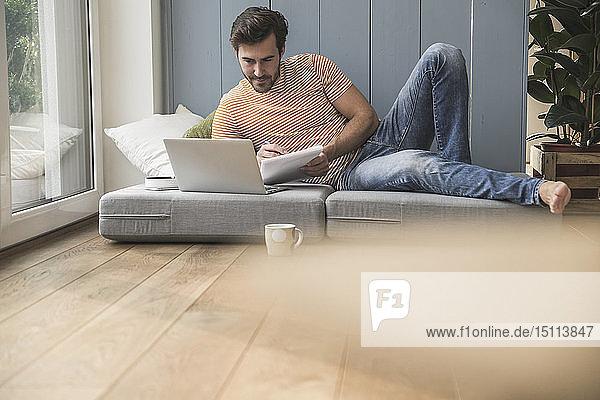 Junger Mann sitzt auf Matratze  benutzt Laptop und macht Notizen