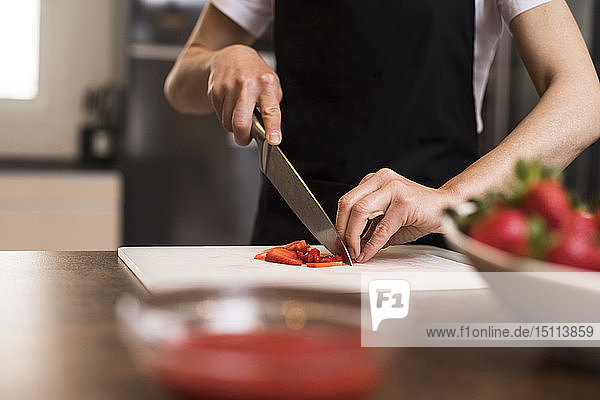 Close-up of woman cutting strawberries with a knife in a kitchen