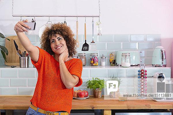 Glückliche Frau  die in Büroküche ein Selfie macht