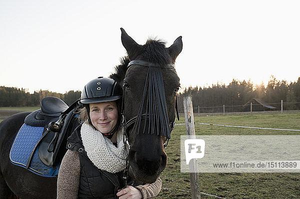 Porträt einer lächelnden Frau mit Pferd