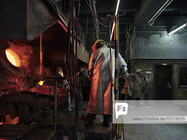Industry  worker at furnace during melting copper  wearing a fire proximity suit