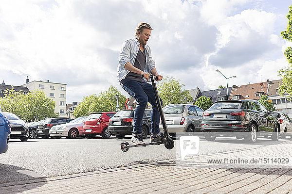 Mann auf E-Scooter springt in die Luft